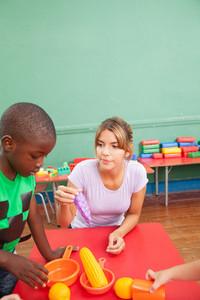 Famale teacher playing with black boy in kindergarten