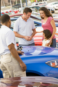 Family choosing new car on lot