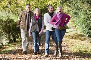 Family group walking through autumn woods
