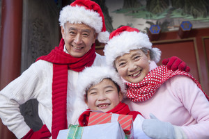 Family holding gifts dressed in holiday attire