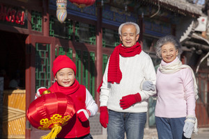 Family holding lantern dressed in holiday attire