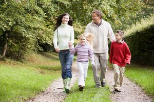 Family on walk through autumn countryside
