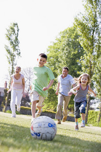Family outdoors playing soccer and having fun