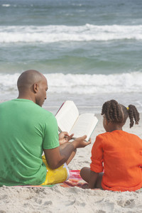 Family reading at the beach