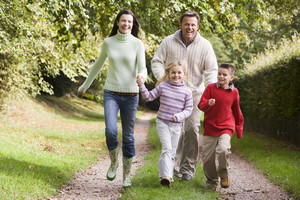 Family running along woodland track in autumn