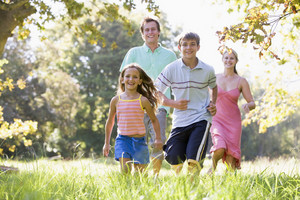 Family running outdoors smiling