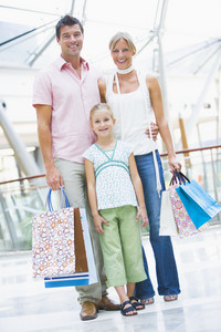 Family shopping in mall carrying bags