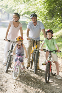 Family sitting on bikes on path smiling