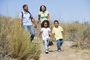 Family walking on path holding hands and smiling