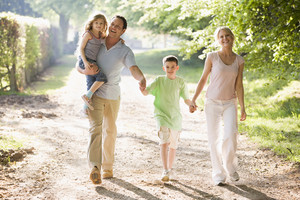 Family walking outdoors holding hands and smiling