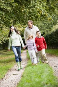 Family walking through autumn countryside