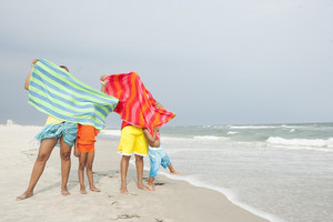 Family with beach towels on beach