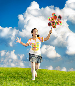 Fantastic scene of happy little girl running and playing carefreely on green meadow in nature