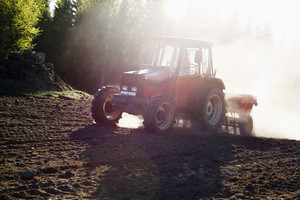 farming tractor in action, sunset