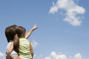 Father and daughter pointing to clouds