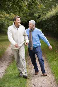 Father and grown up son walking along path through woodland