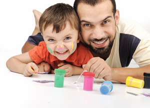 Father and kid playing with paint colors