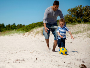 Father and son enjoying a soccer game on the beach