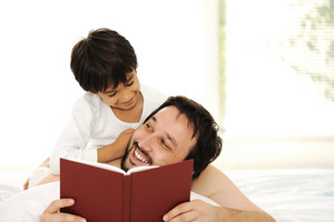 Father and son in bed, reading book together