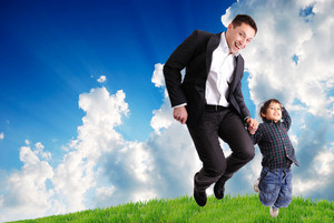 Father and son jumping outdoor on green meadow