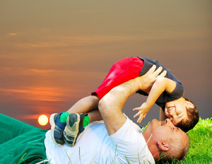 Father and son laying on ground, sunset time