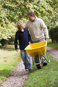 Father and son pushing wheelbarrow along autumn path