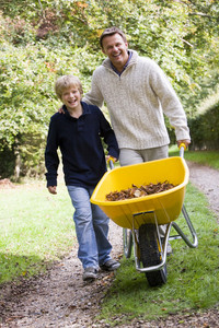 Father and son pushing wheelbarrow along autumn track