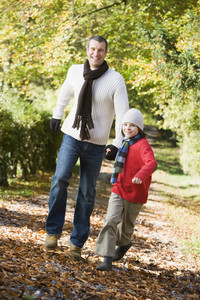 Father and son running along autumn path through trees