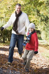 Father and son running along autumn path through woods