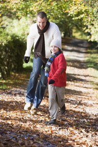 Father and son running along woodland path in autumn