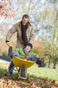 Father giving son ride in wheelbarrowe through autumn leaves
