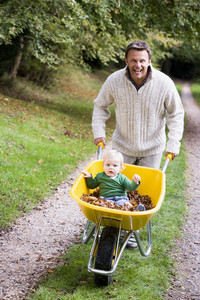Father giving young son ride in wheelbarrow along autumn path