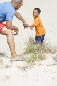 Father helping boy up sand dune