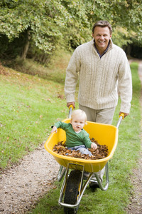 Father pushing young son in wheelbarrow along path