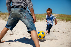 Father together with his young son playing football on the beach