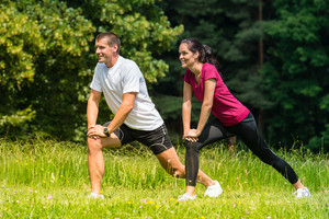 Female and male runner stretching in nature