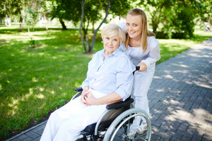 Female caregiver walking with senior patient in park