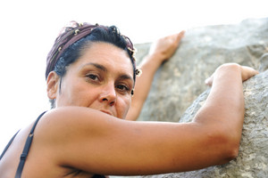 Female climbing rock on the top of mountain