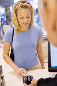 Female customer at checkout enetring PIN number