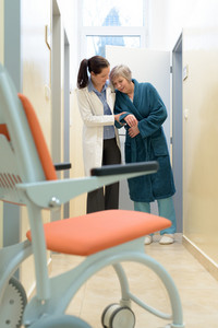 Female doctor helping to walk a senior patient in hospital
