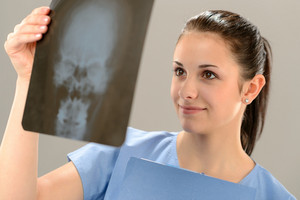 Female doctor holding and examining X-ray picture with skull