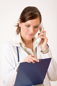 Female doctor on the phone with medical file and stethoscope