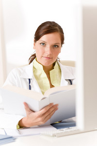 Female doctor read book in clinic sitting at desk