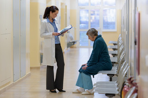 Female doctor reads senior patient files in hospital corridor