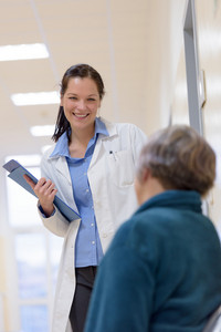 Female doctor smiling to senior patient in hospital