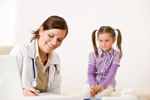Female doctor write prescription for child at clinic