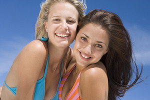 Female friends on beach together wearing swimming costumes