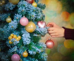 Female hand decorating the christmas tree