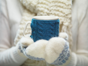 Female hands holding knitted winter mug close up. Woman hands in white and blue mittens holding a cozy knitted cup with hot cocoa