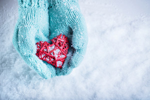 Female hands in teal knitted mittens with a entwined vintage romantic heart on a snow background.
